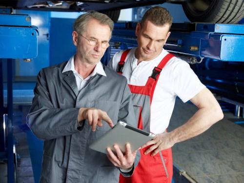 Männliche Führungskraft mit Brille als Meister doer Techniker zeigt einem Arbeiter die Resultate auf einem Tablet